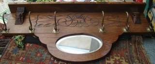 europe a solid oak coat hanger with 6 hooks and a beveled glass mirror