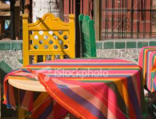 Mexican Cafe Table, Colorful Rainbow Tablecloth, Wooden Chairs Royalty